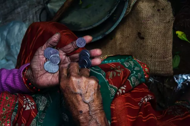 An old woman counting coins.