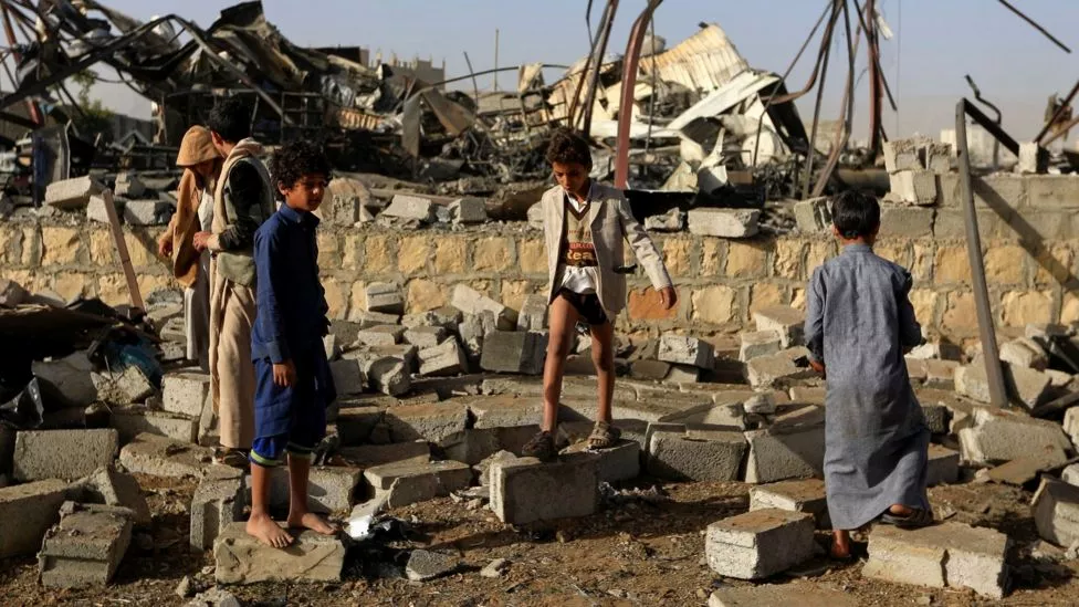Yemeni children standing in the middle of war rubble.