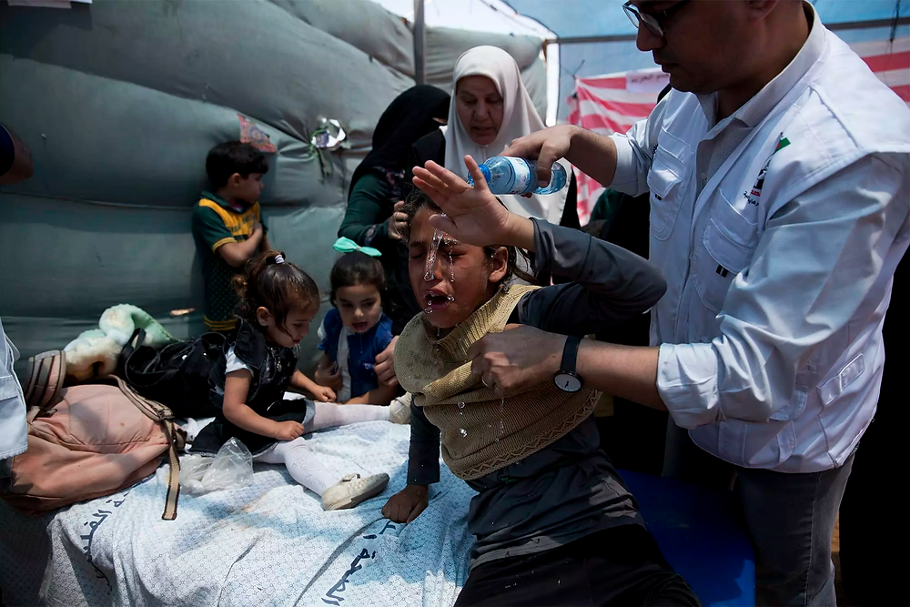 A doctor treating children with water to help them after a tear gas attack.