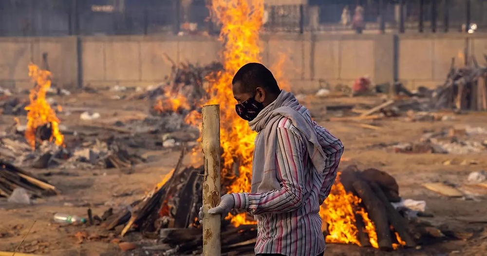 A crematory worker walking past multiple funeral pyres.