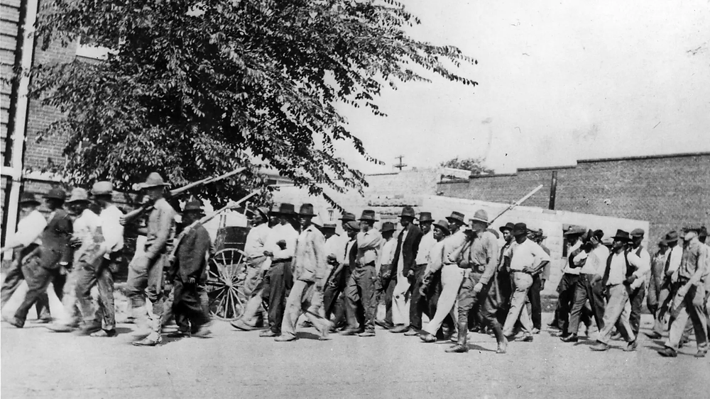 National Guard Troops with rifles escorting the African American men after the massacre.