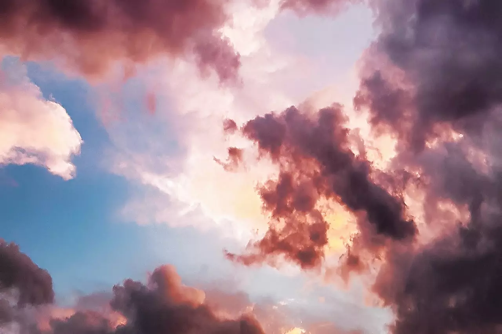 A picture of the sky with white, red, and black clouds.