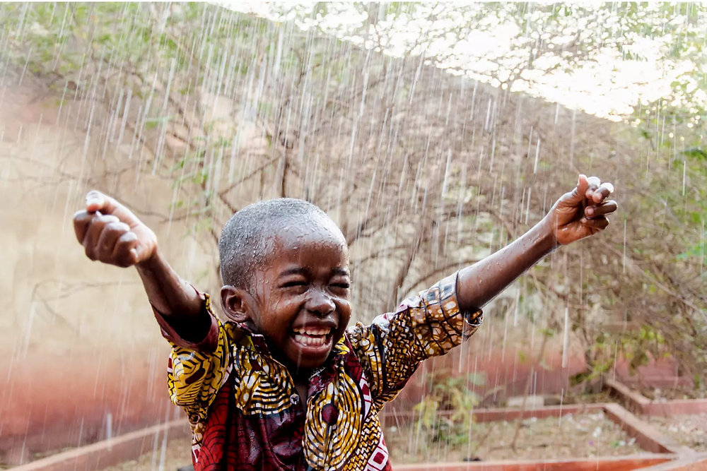 An African boy enjoying rain.