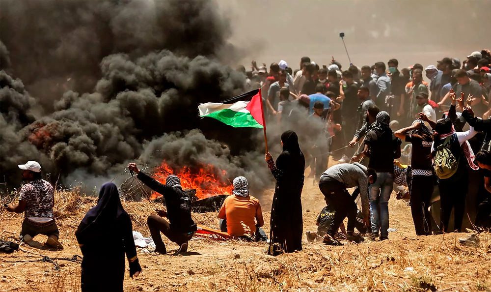 A Palestinian woman holding her national flag looks at clashes with Israeli forces near the border between the Gaza strip and Israel on May 14, 2018.