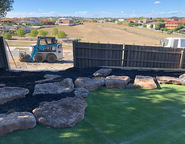 Bobcat, tip truck, rock features, synthetic grass, Greenvale