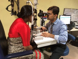 Glaucoma specialist Dr Kumar Ravi examining patient eyes on slit lamp
