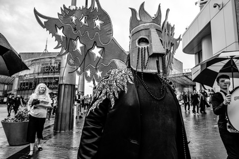 Photo in black and white of a large cardboard mask embeliished with beads and stars, modelled by a person wearing a black suit.