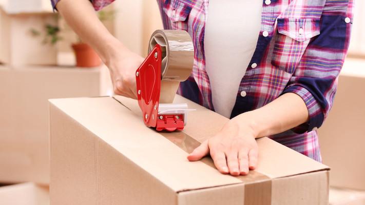 Man taping up a storage box