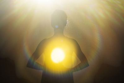 Woman radiating light from within into a