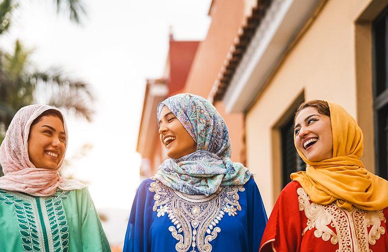 Happy Muslim women walking in the city c