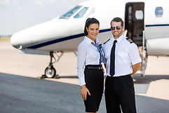 Pilots stand in front of an aircraft and look into the camera with sunglasses