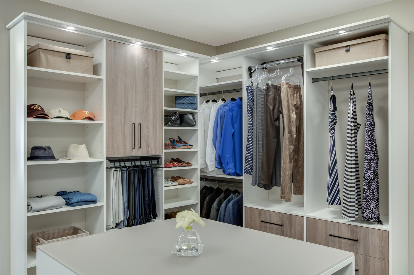 Modern Closet with LED lights, motorized wardrobe lift, pant rack, and island with back painted glass from Closets by McKenry