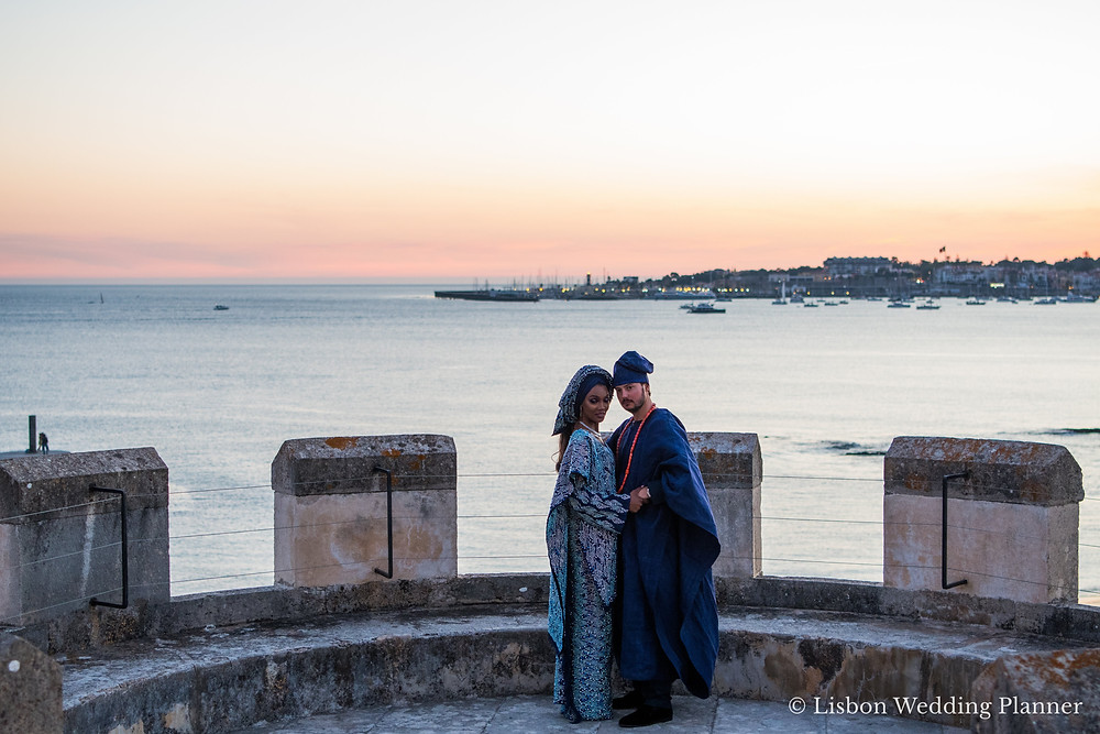 A nigerian couple with nigerian wedding outfits in blue having a destination wedding by the sea in Portugal
