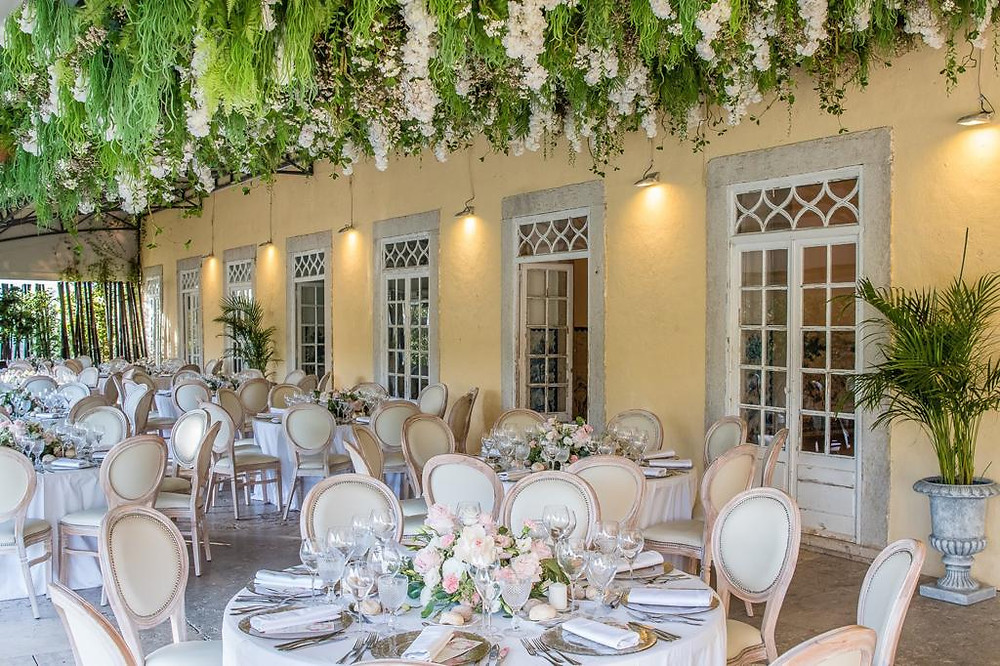 A  wedding dinner in the greenhouse of Quinta do Torneiro with round tables and napolean chairs Vintage Wedding Venue Portugal
