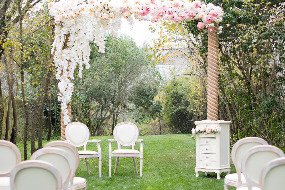 Cerimonia simbolica com arco de flores romantico e cadeiras luxuosas no jardim da entrada da Quinta do Torneiro