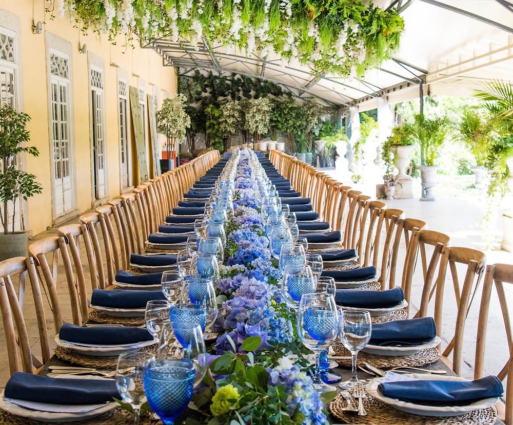 Mesa longa de casamento com cor azul e flores azuis no terraço da Quinta do torneiro