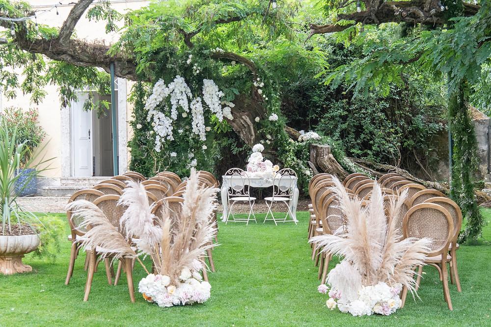 Cerimónia com cadeiras e mesa de madeira rústica decorada com flores de estilho boho e cores neutras na Quinta do Torneiro