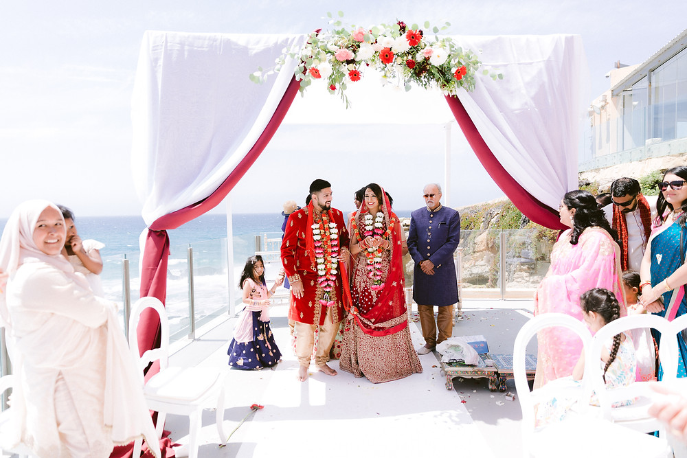 The Wedding Canopy was decorated with white and red fabrics, adorned with greenery and red flowers, matching the Red Royal and Gold Outfits. Arriba by the Sea offers several terraces overlooking the beach and the ocean