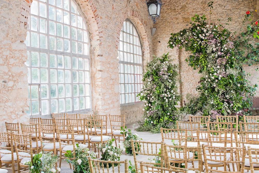 A greenery wedding ceremony inside of the greenhouse of the beach castle forte da cruz