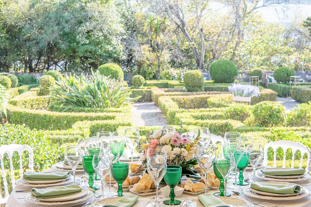 Um jantar de recepção de casamento no terraço coberto e vista para jardim francês da Quinta do Torneiro