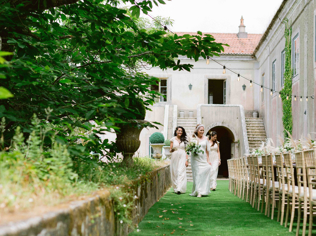 The bride and the bridesmaids walking towards the Boho Wedding Ceremony. The Rustic Boho Outdoor Wedding Ceremony was celebrated inPortugal