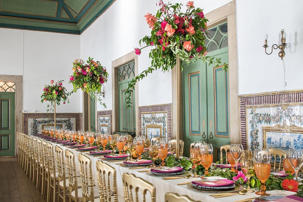 Decoracao de mesa de casamento na sala verde da Quinta do Torneiro com copos coloridos de laranja e flores altas coloridas