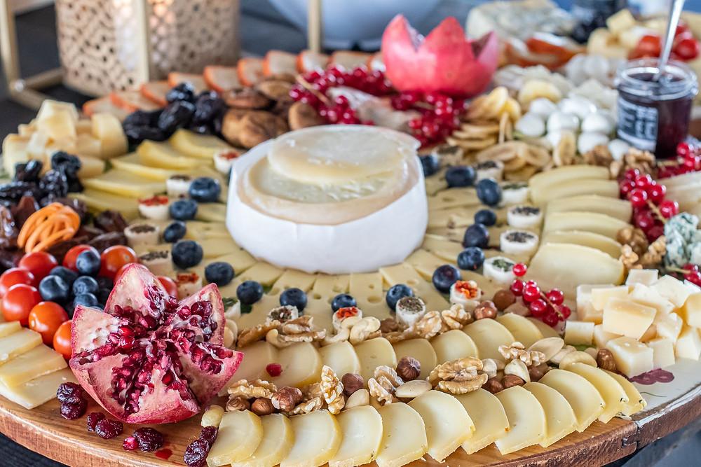 Mesa repleta de conjunto de queijos variados num vasamento na Quinta do Torneiro