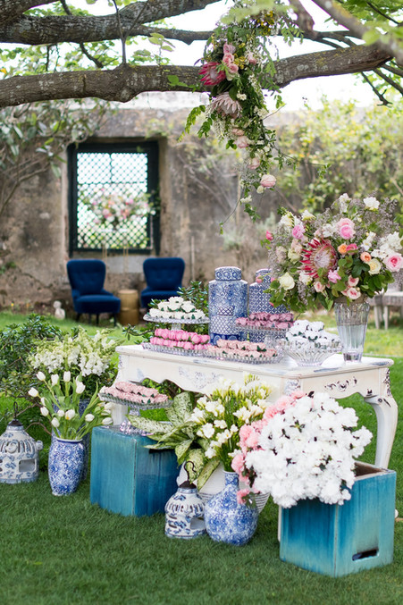 Blue destination wedding inspo. Antique able with blue details and sweets/gifts for guests. Amazing flowers by our exclusive florists