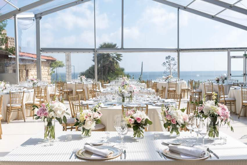 The tables are full of pink and white flowers with a view of the ocean beach