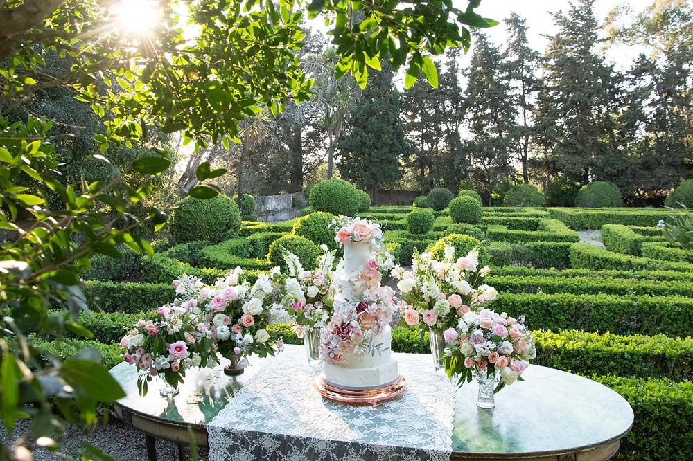 Momento do corte do Bolo de casamento e flores na mesa verde do jardim frances da Quinta do Torneiro