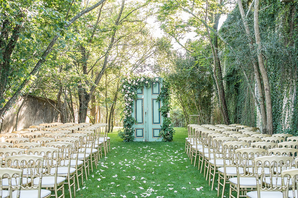 An outdoor wedding ceremony organized in the entrance garden with gold chairs and rustic doors at Quinta do Torneiro Portugal