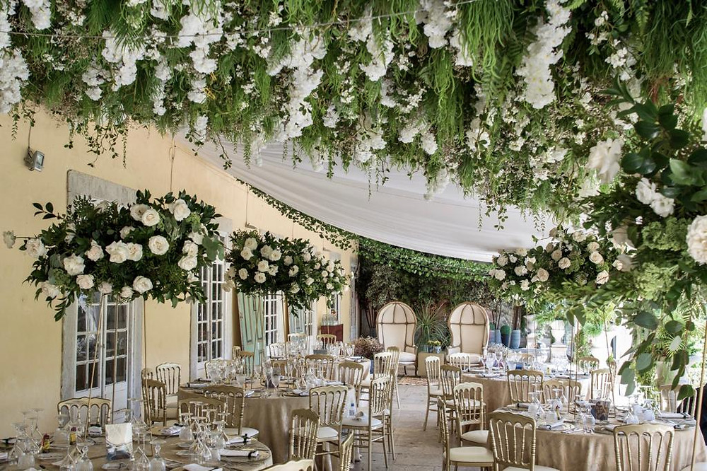 a luxury wedding reception dinner on the greenhouse of Quinta do Torneiro Portugal with tall green flowers and greenery falling from the ceiling
