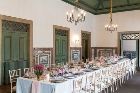 Dinner table decorated with pink seasonal flowers, golden and blue plates, tablecloth and chandeliers matching the beautiful Noble Room of Quinta do Torneiro, Lisbon, Portugal.