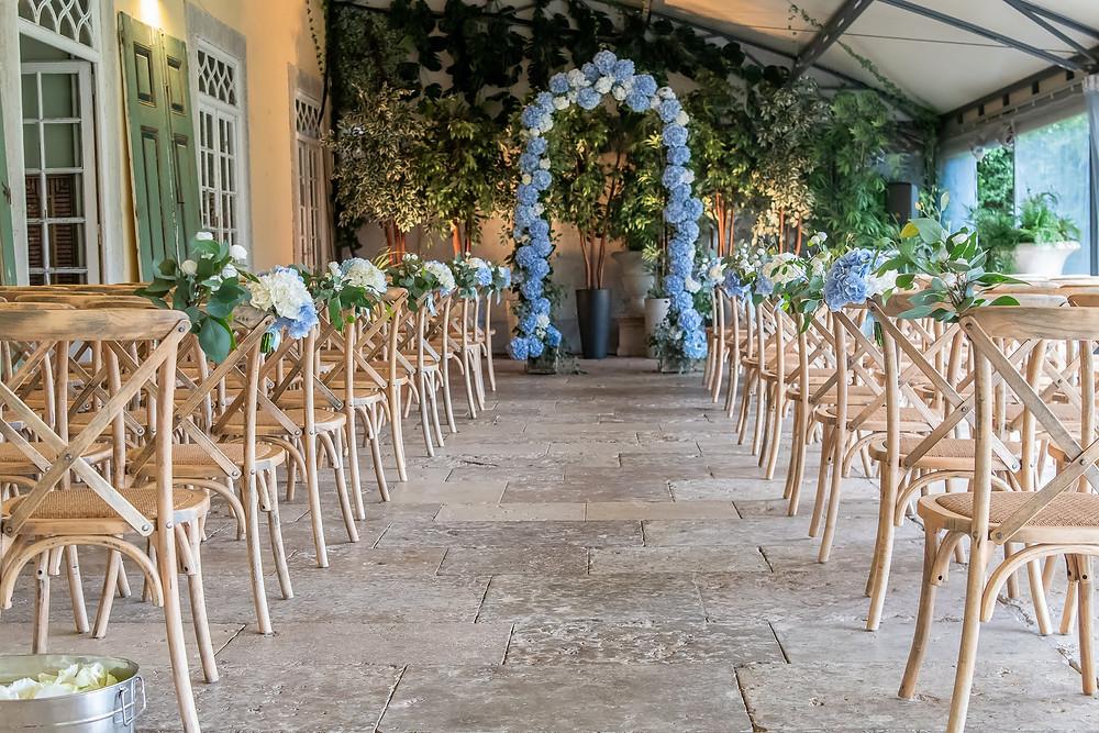Cerimónia no interior do Terraço coberto da Quinta do Torneiro com cadeiras rústica e arco com flores azuis