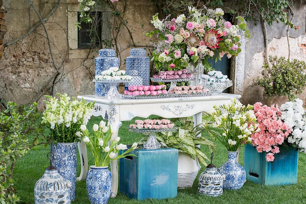 Mesa enfeitada com doces de todos os tipos e flores no jardim da Quinta do Torneiro para um casamento ao ar livre