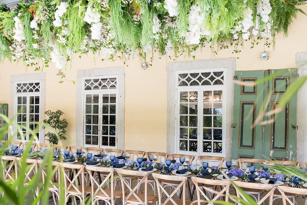 Festa de casamento com mesas de madeiras e tons de azul no terraço çoberto da Quinta do Torneiro