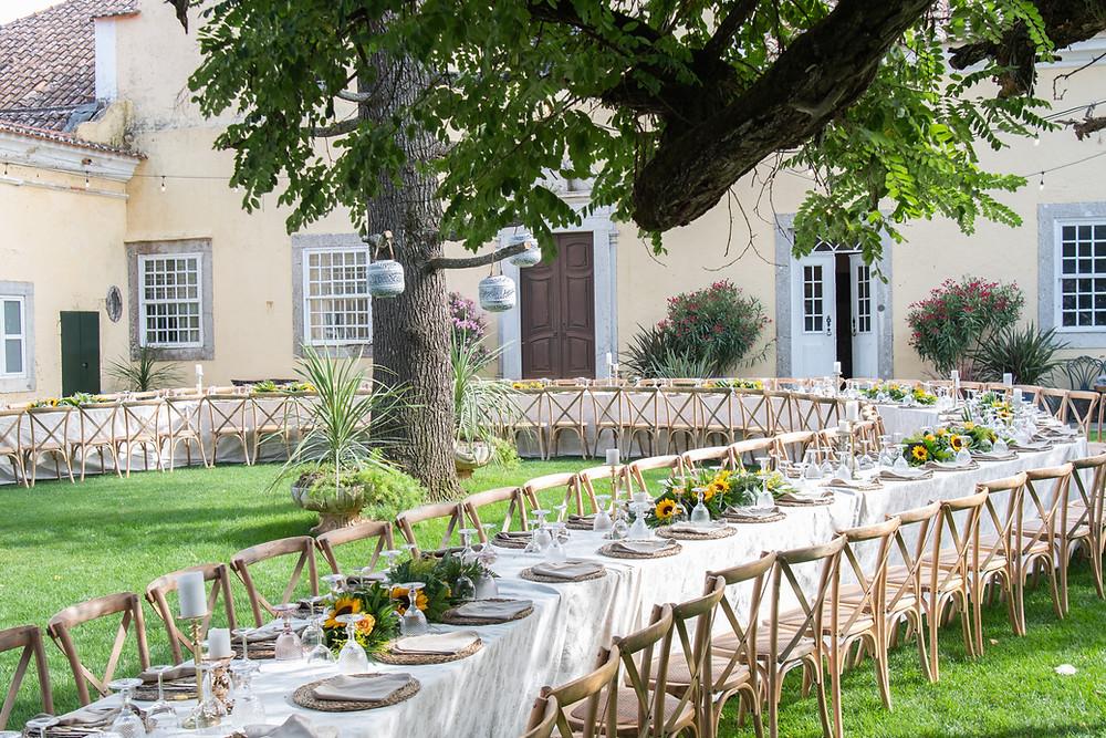Jantar de casamento numa mesa longa com cadeiras de madeiras na Quinta do Torneiro