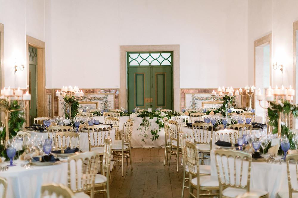 Jantar de casamento na sala verde com mesas redondas e copos azuis na Quinta do Torneiro