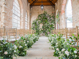 Wedding Ceremony with Greenery Arch and Flower Arragements along the aisle in Portugal