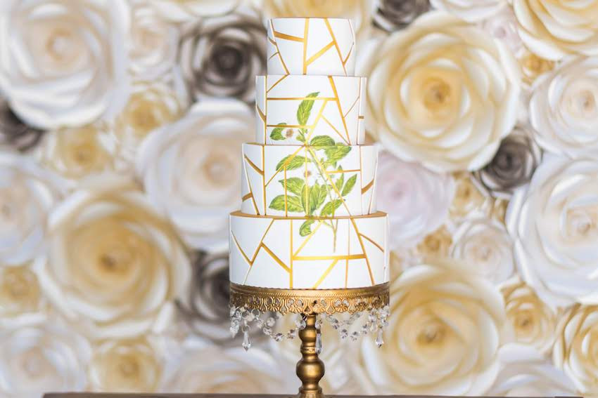 Detailed wedding cake against flower wall. Edible paint with a gold outline on top of a gold stand. The wedding cake, was a beautiful 4 layered cake designed with gold geometrical lines and a greenery illustration, so trendy. With the roses flower wall made a stunning and elegant set for the wedding cake moment!