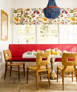 A fabric for valance by Josef Frank with a beaded chandelier and natural rope dining chairs