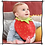 Baby wearing a dribble bib in the shape of a big red strawberry