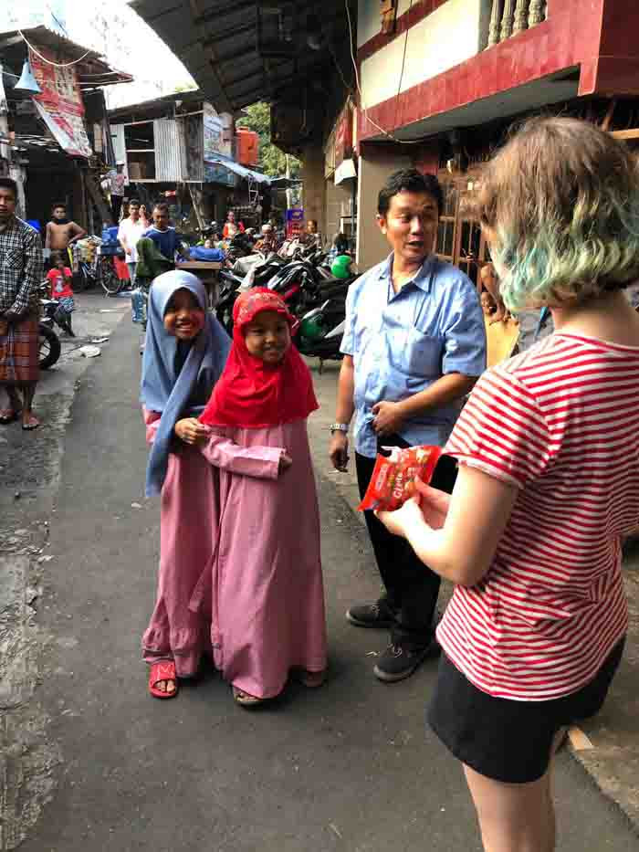 Flossie chats to children and their dad on the streets of Jakarta