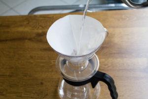 Coloque o filtro no suporte, nesse momento pré-aqueça o recipiente que receberá o café e escalde o filtro com água fervida.