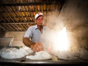 Seu Benedito Cordeiro, dono da fábrica Cuscuz Nordeste colocando massa de cuscuz no fogo enrolada em pano quente. Foto: Jonathan Lins/G1