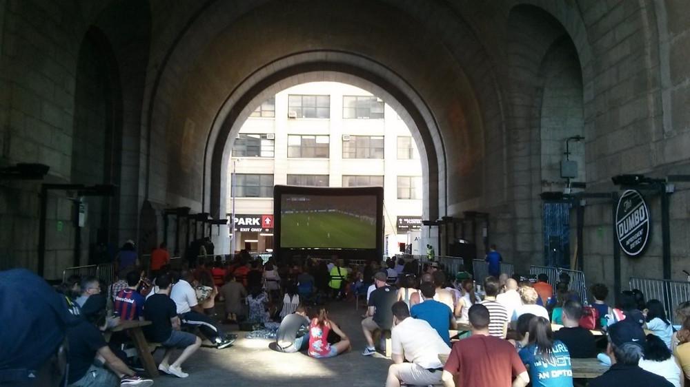תושבים צופים במשחק כדורגל במרחב הציבורי