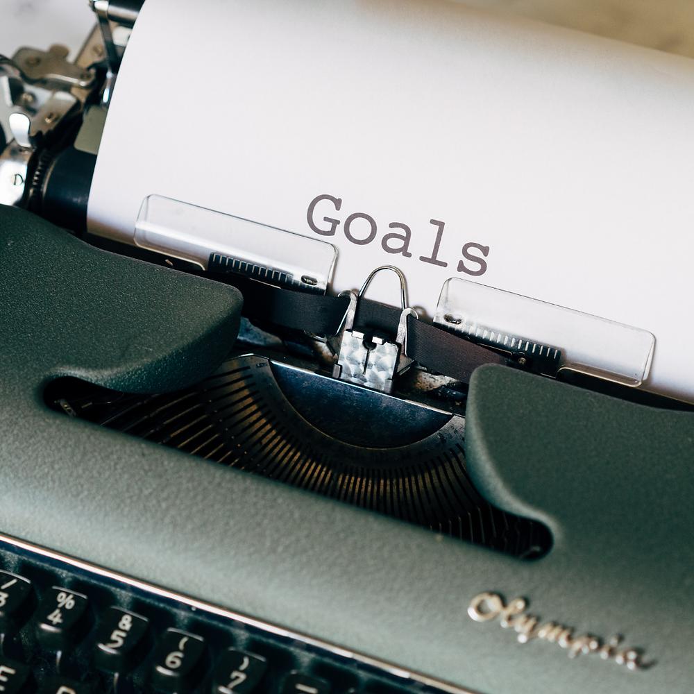 Goals written on green typewriter