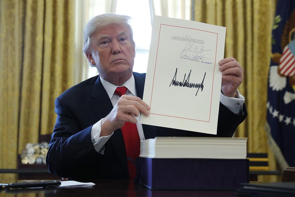 Donald Trump holding up tax cut bill after signing December 2017