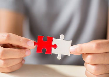 hand-connecting-two-puzzle-pieces-table-