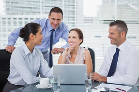 cheerful-colleagues-around-laptop-workin